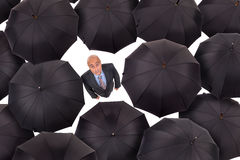 Businessman with umbrellas Stock Image