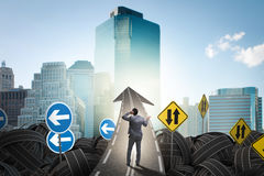 Businessman in uncertainty concept on road intersection crossroa Royalty Free Stock Image