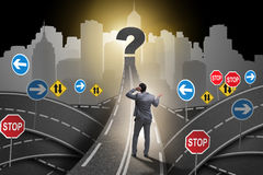 Businessman in uncertainty concept on road intersection crossroa Stock Photo