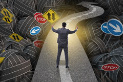 Businessman in uncertainty concept on road intersection crossroa Stock Image