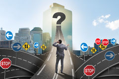 Businessman in uncertainty concept on road intersection crossroa. Ds Royalty Free Stock Image