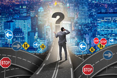 Businessman in uncertainty concept on road intersection crossroa. Ds Stock Photos