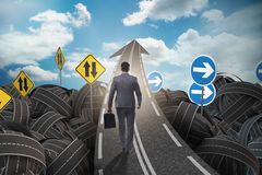 Businessman in uncertainty concept on road intersection crossroa. Ds Stock Photo