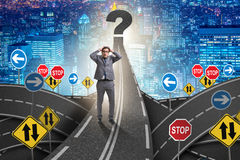 Businessman in uncertainty concept on road intersection crossroa. Ds Royalty Free Stock Photos
