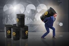 The businessman under the burden of oil barrel. Businessman under the burden of oil barrel Stock Image