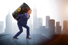 The businessman under the burden of oil barrel. Businessman under the burden of oil barrel Stock Photo
