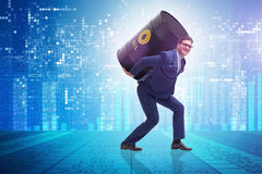 The businessman under the burden of oil barrel. Businessman under the burden of oil barrel Royalty Free Stock Photos