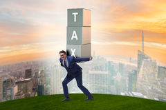 The businessman under heavy tax burden Stock Photo
