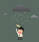Businessman under a little umbrella in the rain Royalty Free Stock Photos
