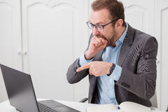 Businessman under stress after realized that he made a mistake. Young executive bites his fist while looking at laptop, angry because something go wrong stock photo