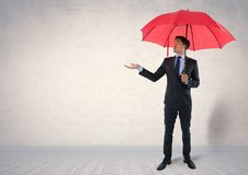Businessman under umbrella in room Royalty Free Stock Images