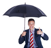 Businessman under umbrella shows thumb up Stock Photo