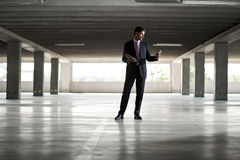 Businessman in underground parking. Holding tablet and mobile phone Royalty Free Stock Photos