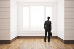 Businessman in unfurnished room. Businessman standing in unfurnished white room with wooden floor, city view and daylight. 3D Rendering Stock Photography