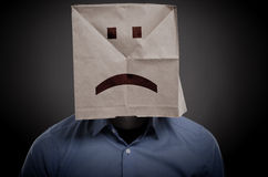 Businessman with an unhappy face on a paper bag. Negative concept image royalty free stock photo