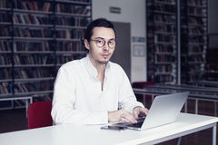 Businessman, university student wearing white shirt and eyeglasses, in a public co-working or library writing and working at lapto Royalty Free Stock Photo