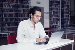 Businessman, university student  writing and working at laptop, in a public co-working or library Royalty Free Stock Photo