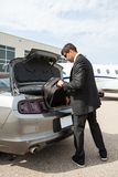 Businessman Unloading Luggage From Car At Airport. Full length of businessman unloading luggage from car boot at airport terminal Stock Photos
