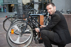 Businessman unlock his bike after a day of work Stock Photo