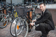 Businessman unlock his bike after a day of work Stock Images
