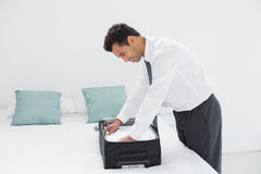 Businessman unpacking luggage at hotel bedroom Royalty Free Stock Photos