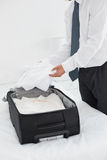 Businessman unpacking luggage at a hotel bedroom Stock Photos