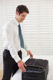 Businessman unpacking luggage at a hotel bedroom Royalty Free Stock Image