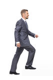 Businessman up the staircase over white background. Businessman in suit  following up  over the white background Royalty Free Stock Photo