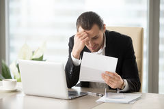 Businessman upset because of bank debt notice. Stressed businessman upset because of bank letter with warnings about loan debt. Sad guy worries about financial stock image