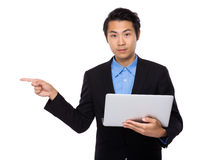 Businessman use of laptop and finger point aside Royalty Free Stock Photography