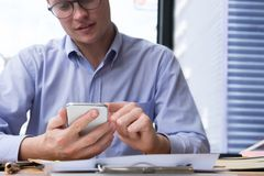 Businessman use mobile phone at workplace. man texting message o. Businessman use mobile phone at workplace. young man texting message on smart phone at office Stock Photography