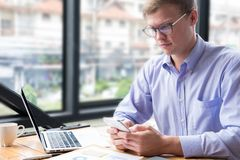 Businessman use mobile phone at workplace. man texting message o. Businessman use mobile phone at workplace. young man texting message on smart phone at office Stock Image
