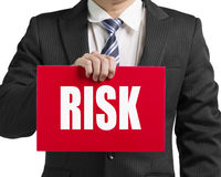 Businessman use one hand to hold a red board with word. Risk close up in white background Stock Photos