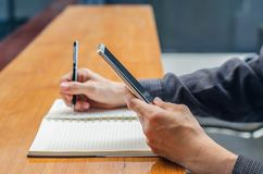 Businessman use smartphone while making notes in notebook. Student learning online. Man using gadget Royalty Free Stock Photos