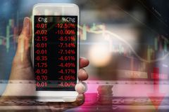 Businessman use smartphone trading online forex or Stock exchange market board data screen mobile with hand / Stock crisis falls. Red charts graph analysis royalty free stock image
