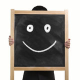 Businessman use two hands to lift up dirty wooden chalk board wi. Th drawing smile face in white background Stock Image