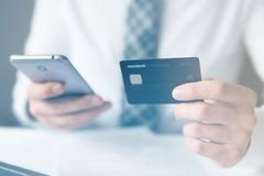 Businessman uses credit card and a smartphone for online payment. Shopping online. stock photo