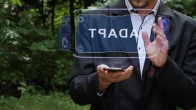 Businessman uses hologram with text Adapt