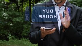 Businessman uses hologram with text Buy house. Unrecognizable businessman activates conceptual HUD holograms on smartphone with text Buy house. Bearded man in a stock video