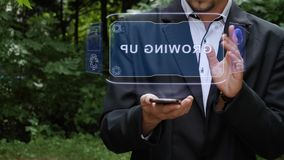 Businessman uses hologram with text Growing UP. Unrecognizable businessman activates conceptual HUD holograms on smartphone with text Growing UP. Bearded man in stock footage