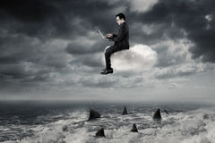 Businessman uses laptop on cloud above sea Royalty Free Stock Photos