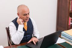 Businessman uses laptop, at desk, at work. royalty free stock photography