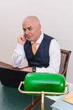 Businessman uses laptop, at desk, at work. Royalty Free Stock Photos