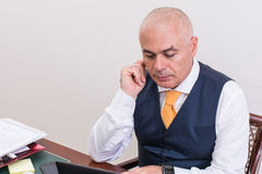 Businessman uses laptop, at desk, at work. Royalty Free Stock Photo