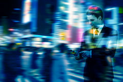 Businessman uses the smart phone on the city street. Double exposure of businessman uses the smart phone on the city street, and motion blur background royalty free stock photo