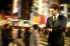 Businessman uses the smart phone on the city street. Double exposure of businessman uses the smart phone on the city street, and motion blur background stock photo