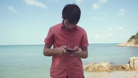 Businessman uses smart phone standing near the tropical beach. slow motion. 1920x1080. Man uses smart phone standing near the tropical beach. slow motion stock footage