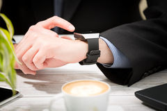 Businessman uses smart watch and phone. Royalty Free Stock Photography