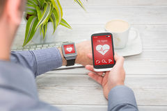 Businessman uses smart watch and phone. Royalty Free Stock Photos