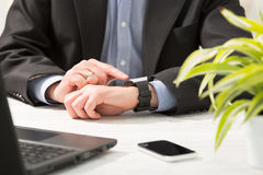 Businessman uses smart watch and phone. Royalty Free Stock Images